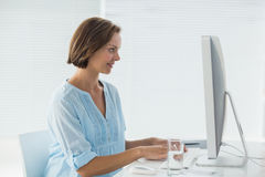 Woman working on computer. Smiling woman working on computer in office Royalty Free Stock Photos