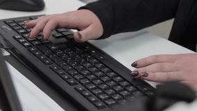 A woman working at a computer typing on the keyboard stock video footage