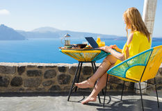 Woman working on computer while on vacation in Mediterranean Royalty Free Stock Photo