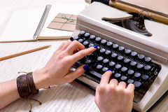 Woman working at contemporary device for writing. Close up of female hands typing on typewriter. Envelop and open notebook are near apparatus Royalty Free Stock Photos