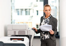 Woman working on copy machine Stock Images