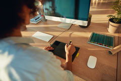 Woman working at creative workplace. Close up of young female designer using graphics tablet and computer. Woman working at creative workplace Stock Photos