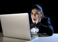 Woman working in darkness on laptop computer late at night surprised in shock and stress. Young hispanic business woman or student girl working in darkness on Royalty Free Stock Photos