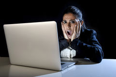 Woman working in darkness on laptop computer late at night surprised in shock and stress. Young hispanic business woman or student girl working in darkness on Royalty Free Stock Image