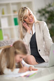 Woman working while daughter is drawing Stock Photography