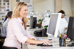 Woman Working At Desk In Busy Creative Office Royalty Free Stock Photos