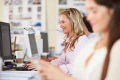 Woman Working At Desk In Busy Creative Office Stock Photo