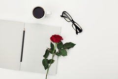Woman working desk with morning cup of coffee, pencil, empty notebook, glasses and rose flower on white table from above. Flat lay Royalty Free Stock Image