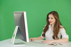 Woman Working on Desktop Computer. Young brunette woman looking at computer screen while working on a desktop computer with green background Stock Photo