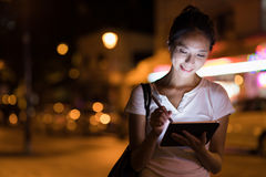 Woman working on digital tablet in the city at night. Asian young woman Stock Photos