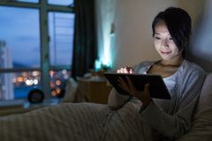 Woman working on digital tablet computer at night. Asian young pretty woman at outdoor Stock Photo