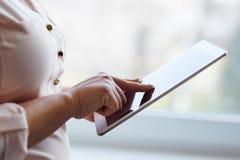 Woman working on a digital tablet near a window. In office stock photo
