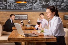 Woman working and drinking wine at lunch in cafe. Royalty Free Stock Photography