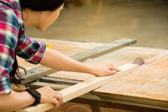 Woman working on an electric buzz saw. Woman carpenter working on an electric buzz saw cutting some boards wearing smartwatch. mixed race asian chinese model stock image