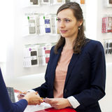Woman working in an electronics store Stock Images