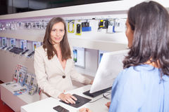 Woman working in electronics store with a customer Royalty Free Stock Images
