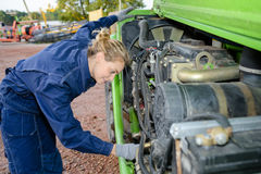Woman working on engine plant machinery. Woman working on engine of plant machinery Stock Photos