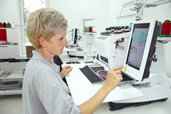 Woman working in a factory. Woman working on computerized machine embroidery in a factory stock photos