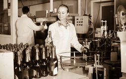 Woman  working on final section of wine production on factory Stock Photos