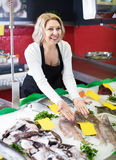 Woman working in fish store Royalty Free Stock Image