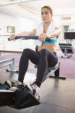 Woman working on fitness machine at gym Royalty Free Stock Photos