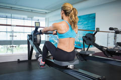 Woman working on fitness machine at gym Stock Photography