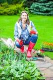 Woman working in a flower garden Stock Photos