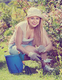 Woman working in garden using horticultural instruments on summe. Glad young blond smiling woman working in garden using horticultural instruments on summer day Stock Photography