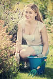 Woman working in garden using horticultural instruments on summe. Happy blond smiling woman working in garden using horticultural instruments on summer day Stock Photography