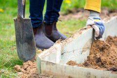 Woman with working gloves and shovel standing in a garden next t Royalty Free Stock Photos