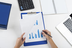 Woman is working with a graph. Top view of woman's hands. She is looking at blue graph in notepad and making notes on it. Concept of statistician's work. Mock up Stock Image