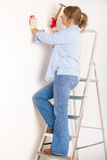 Woman working with hammer. Driving a nail in white wall in home, wearing protective gloves and glasses Royalty Free Stock Photos