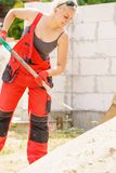 Woman using shovel on constriction site stock photography