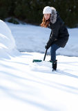 Woman working hard to shovel snow. An attractive young woman looking down while shoveling her driveway Royalty Free Stock Photo