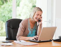 Woman working on her computer while she is phoning Royalty Free Stock Image