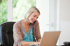 Woman working on her computer while she is phoning Royalty Free Stock Images