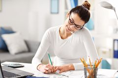 Woman working in her home office. Picture showing young woman working in her home office Royalty Free Stock Photos