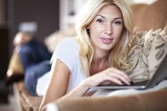 Woman working in her laptop. Beautiful blond young woman working on her laptop computer Royalty Free Stock Photo