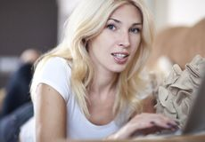 Woman working in her laptop. Beautiful blond young woman working on her laptop computer Stock Photography