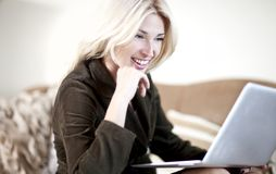 Woman working in her laptop. Beautiful blond young woman working on her laptop computer Royalty Free Stock Photography