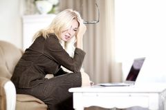 Woman working in her laptop. Beautiful blond young woman working on her laptop computer Royalty Free Stock Images
