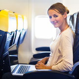 Woman working on her laptop computer on board of an airplane Stock Photo