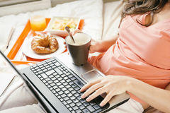Woman working with her laptop computer and having breakfast Stock Images