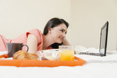 Woman working with her laptop computer and having breakfast. Royalty Free Stock Photos