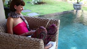 Woman working on her laptop computer sitting in the armchair at the poolside, Bali island. stock video footage