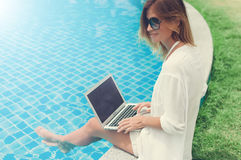 Woman working on her laptop computer sitting at poolside. Woman freelancer working on her laptop computer sitting at poolside Royalty Free Stock Image