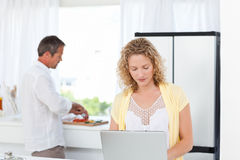 Woman working on her laptop while her husband Stock Photo