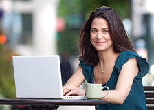 Woman working on her laptop at sidewalk care Stock Photo