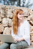 Woman working on her laptop sitting thinking Stock Photography