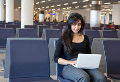 Woman working with her notebook in the airport Royalty Free Stock Photos